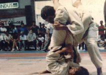 Aplicando um armlock em luta realizada pelo carioca de jiu-jitsu ao fundo GM Helio Gracie assistindo